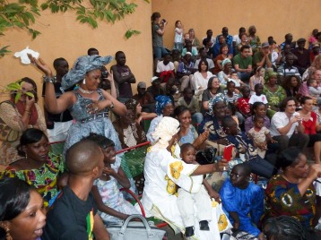 Singer Amy Sacko dances in the audience as her daughter Oumou and niece Salimata perform a song by Mah Bara Soumano (seen bottom left)